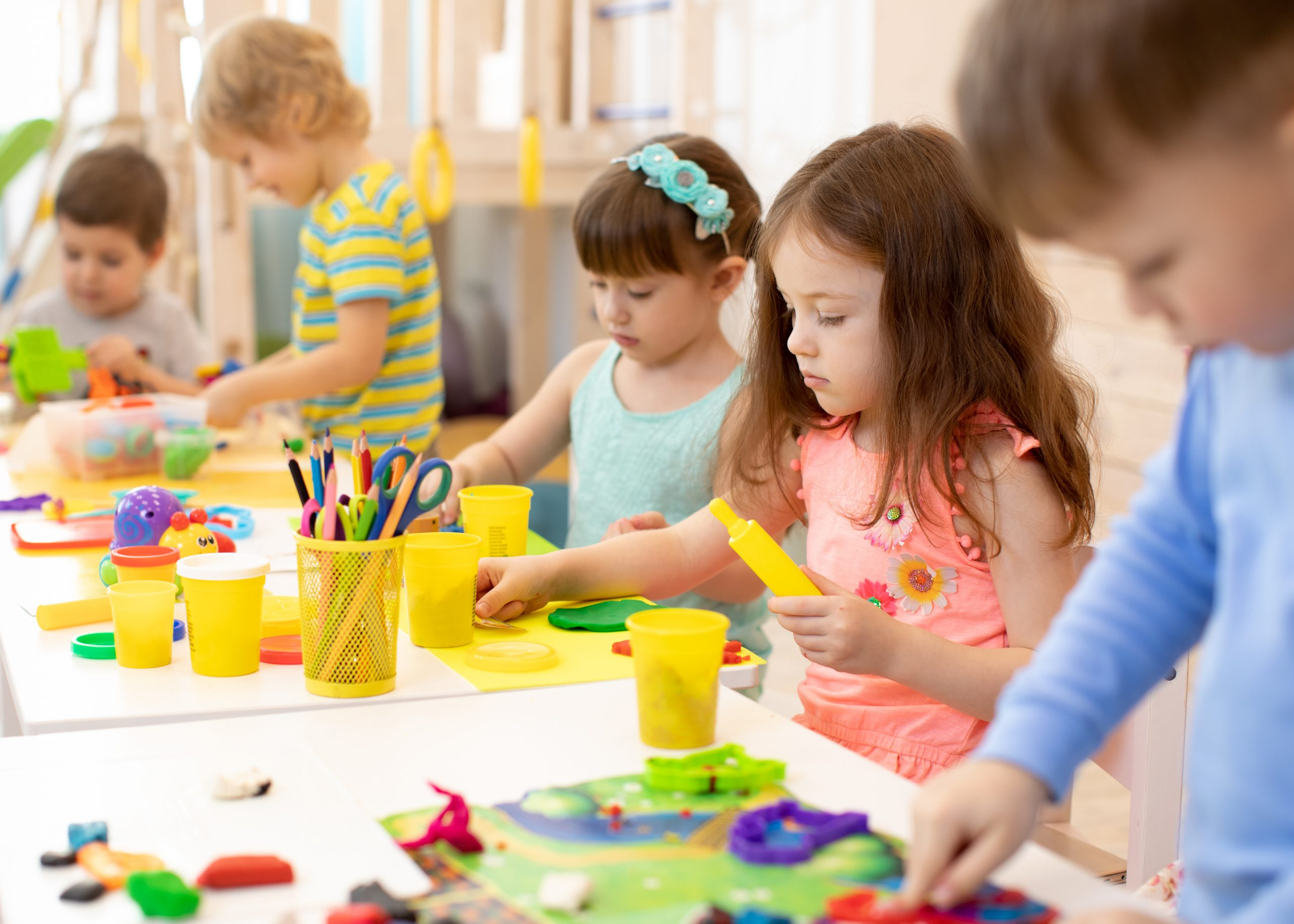 Art and craft activity in kindergarten. Preschool kids hands working in day care center. Group of children engaged in handcrafts